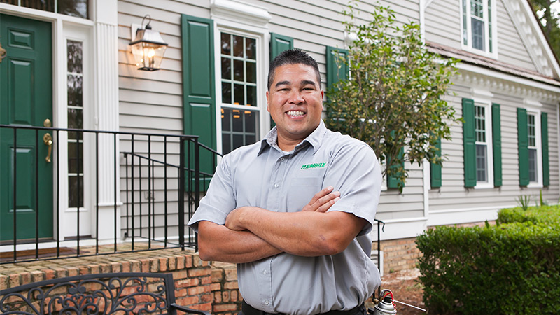 terminix employee standing in front of the green door